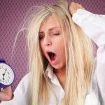 tired-woman-with-alarm-clock